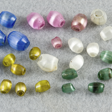 Blown glass beads sparkle after being cleaned by hand, c. 2013