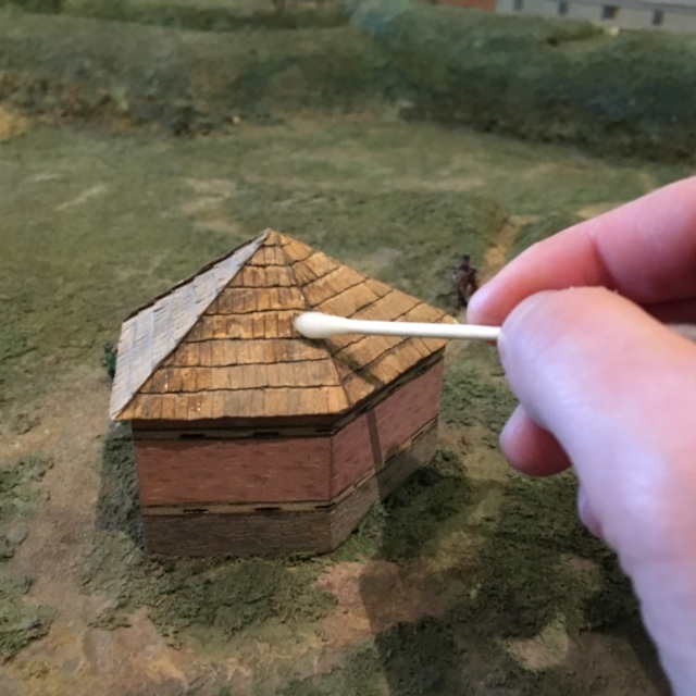 Close-up of using a Q-tip to clean the Fort Pitt Block House roof.