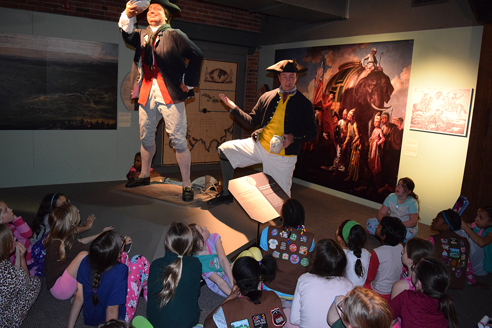 Girl Scouts talk with an 18th century sailor from the Royal Navy.