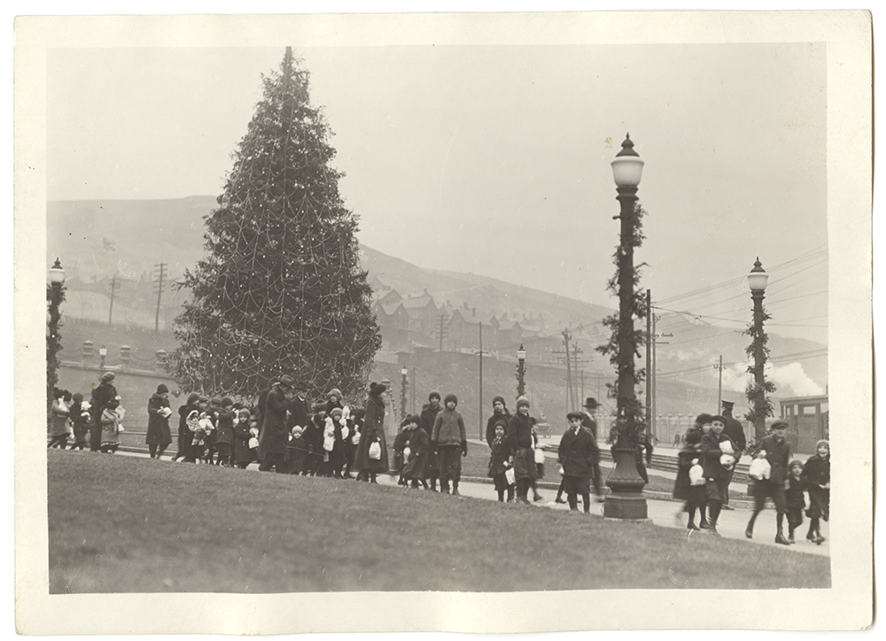 """The children of employees at the Edgar Thompson Works file past a giant Christmas tree holding their annual """"holiday treat."""" 