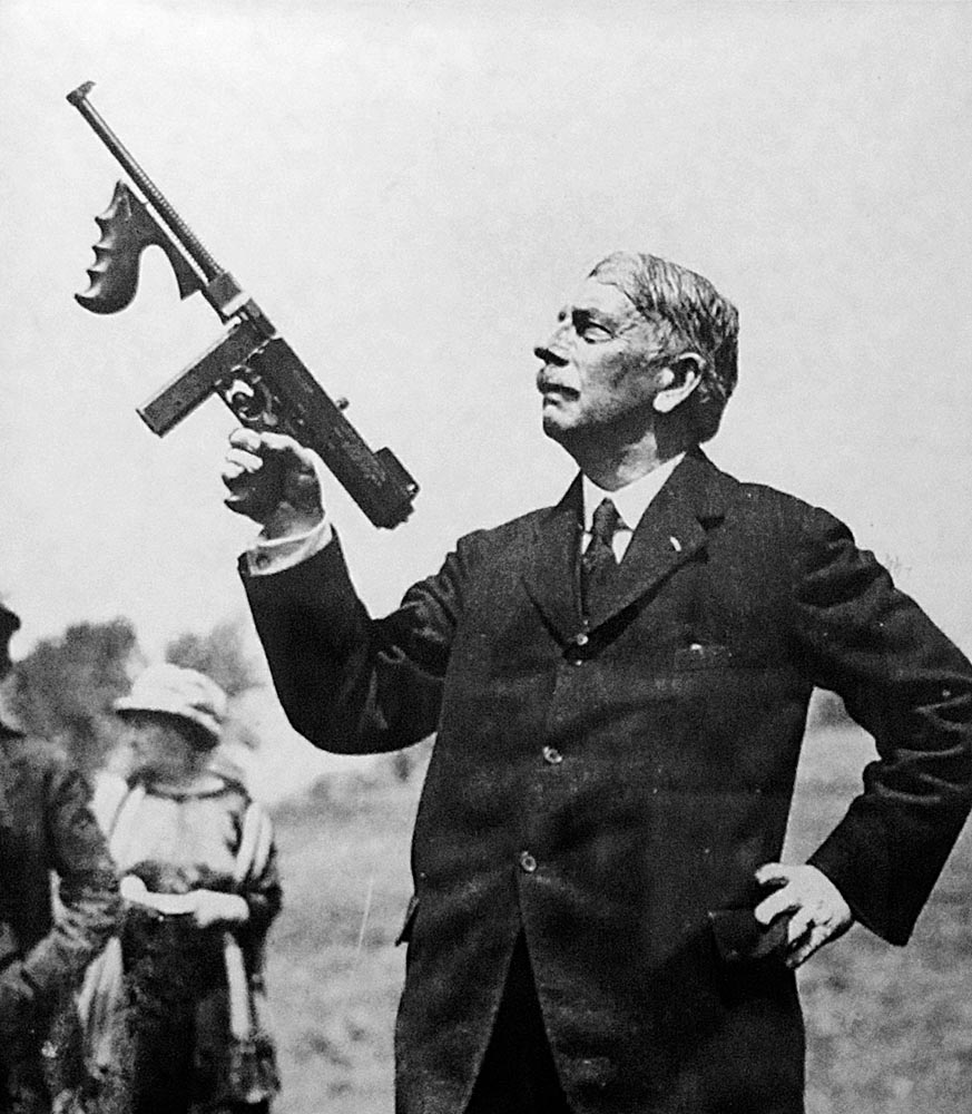 General John T. Thompson holds an M1921 Thompson submachine gun.