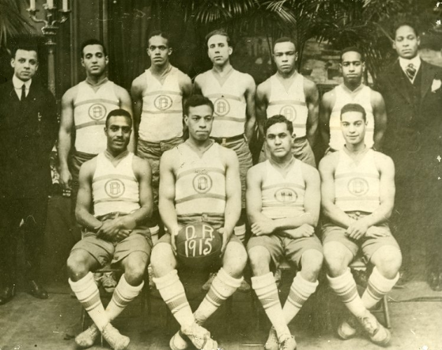 """Big Jim,"" holding the basketball, poses with the Delaney Rifles basketball team, 1915."