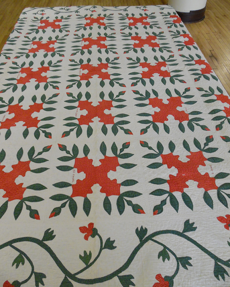 "Quilt, cotton, 100"" x 100"", signed and dated 1852, Beaver County, Pennsylvania. Twenty-five squares appliqued in red and green with scrolling stem, leaf and flower border."