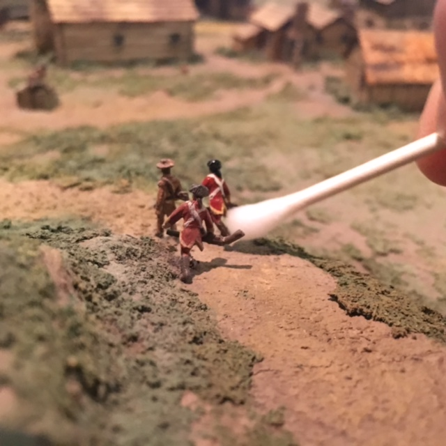 Cleaning soldier figures with a Q-tip.