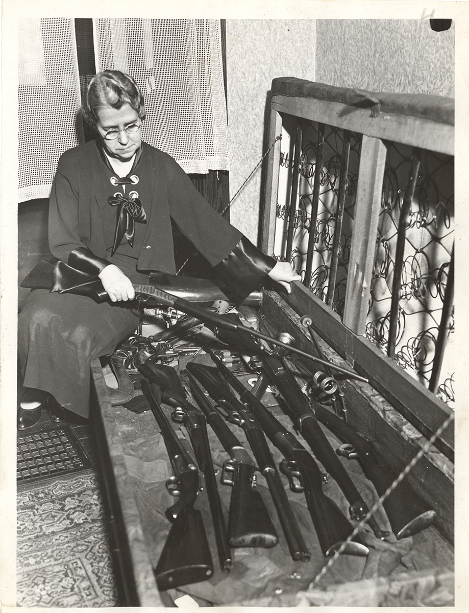Unidentified woman with guns hidden under box frame mattress, c. 1930. | Heinz History Center
