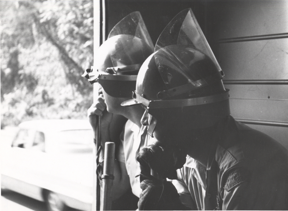Two unidentified policemen don riot helmets with attached face shields from the 1960s.
