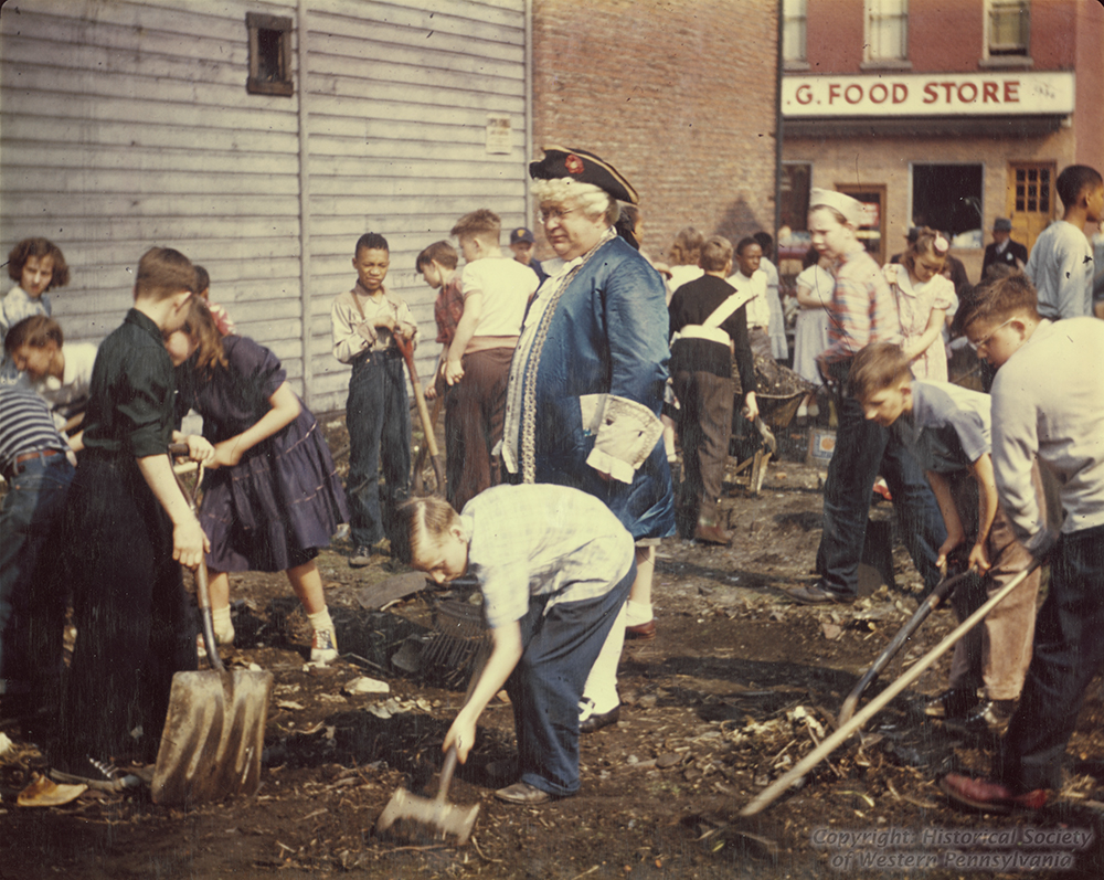 Dressed in his colonial finest, Pa Pitt oversees a group of Pittsburgh school children cleaning up a vacant lot, late 1940s. | Heinz History Center