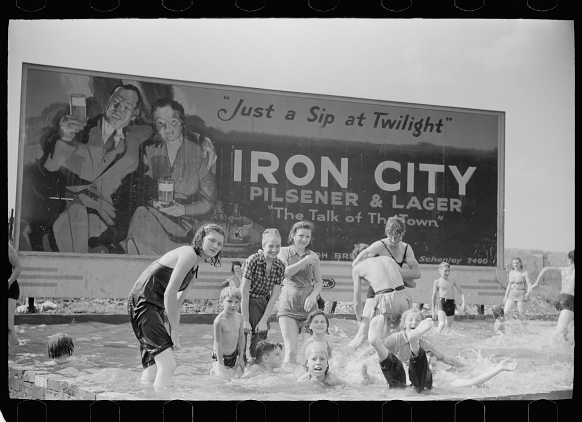 Local children enjoy a dip in the pool in front of an Iron City billboard, July 1938. Photo by Arthur Rothstein, courtesy of the Library of Congress.