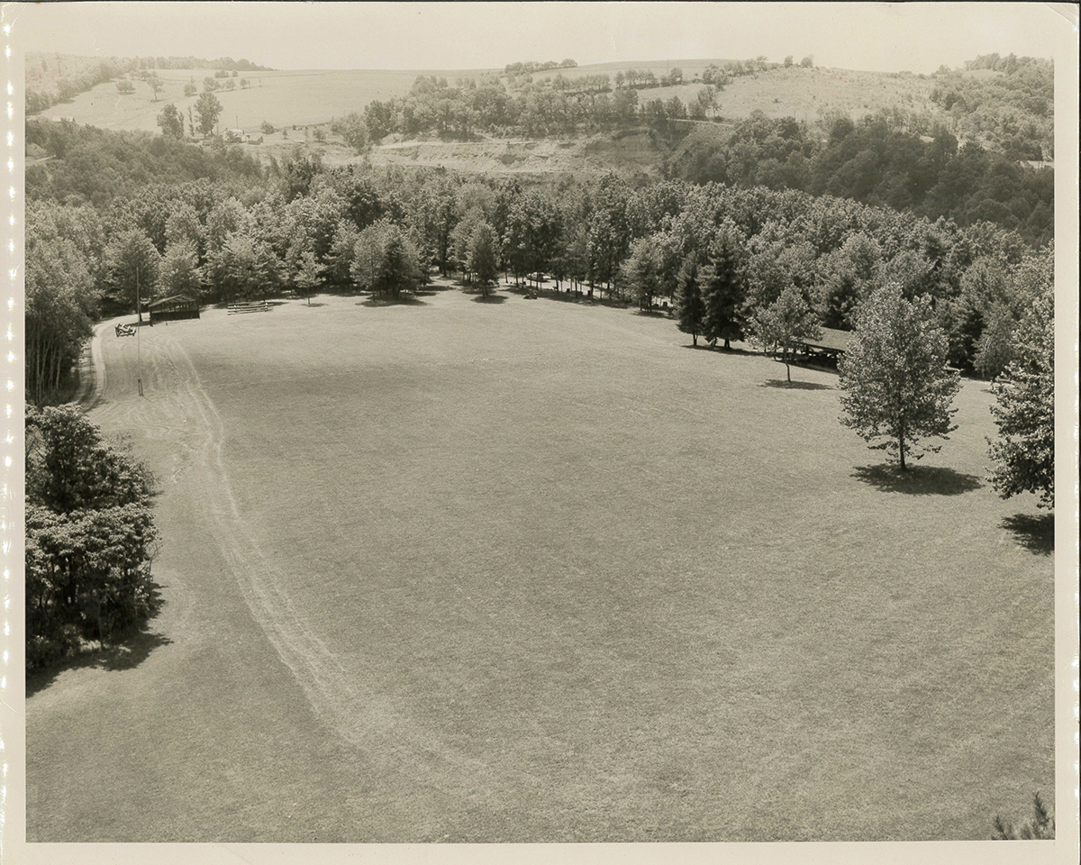This photograph was taken from the top of the Green towards where the Visitor Center is today. The softball diamond can be seen on the left. The parking lot and camping area at the bottom of the green and the pavilion, which stands today, on the right.