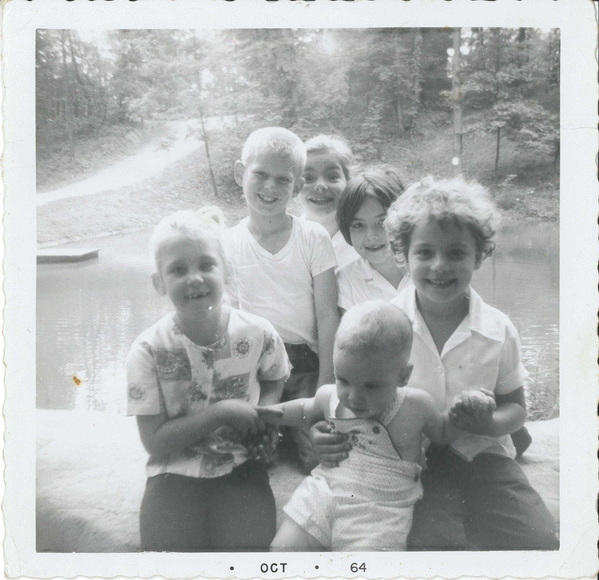 "From the back of the photograph: ""Taken the last day of school June – 64. Terri and Barry Andrews. Patience, Francie, Erin(?) and Danny at the Pond on Miller Property later Meadowcroft Village."" The blacksmith shop, still there today, would be finished that July on the hill directly across the pond."