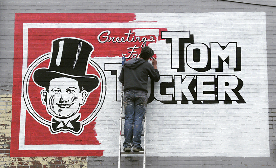 A new Tom Tucker wall sign was painted in 2012 by muralist Anthony Purcell on the side of Comet News in Braddock. He's painted and restored dozens of wall signs throughout the city. Courtesy of Anthony Purcell.