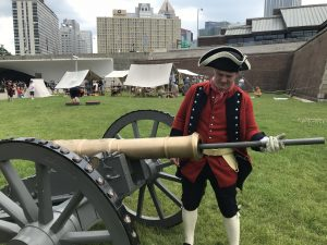 Costumed 18th century reenactor loads a cannon at the Fort Pitt Museum.