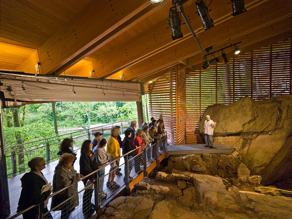 Dr. James Adovasio explains the site to a group of visitors. The large rock behind him is a roof collapse which took place 12,000 years ago.