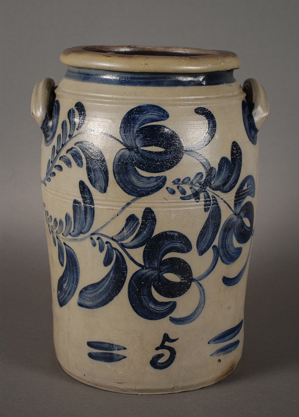 Cylindrical five-gallon stoneware storage jar. Exterior has gray salt glaze and cobalt freehand decoration in floral patterns. Made by James Hamilton and Company, c. 1860. On display in the Special Collections Gallery. Gift of Sandra Palmer.