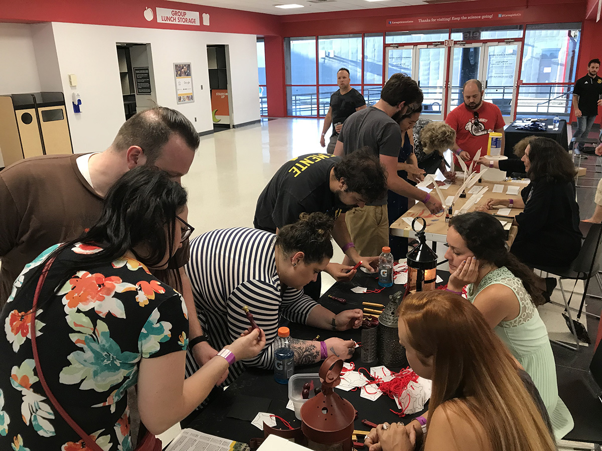 Branwyn (foreground) helps guests at the Science Center's 21+ Night Block Party. Branwyn represented the Fort Pitt Museum and helped guests make wax seals.