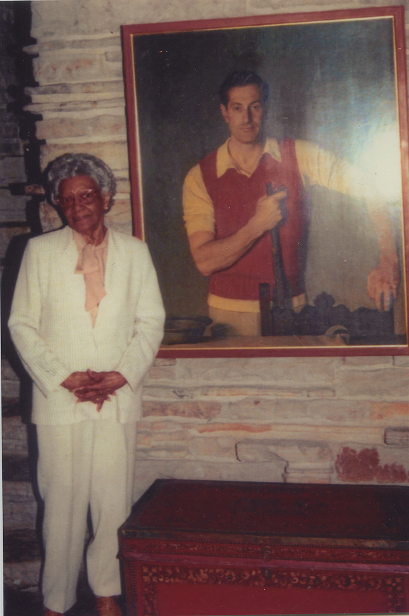 Elsie Henderson stands alongside a portrait of Edgar Kaufmann, Sr. during a visit to Fallingwater. Elsie Henderson Papers and Photographs, Detre Library & Archives, Heinz History Center.