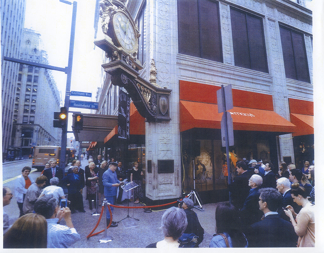 """Henderson (lower left corner wearing blue) is celebrated by David Newell (dressed as Mr. McFeely from """"Mister Rogers' Neighborhood"""") under the Kaufmann's Department Store clock for her birthday. Elsie Henderson Papers and Photographs, Detre Library & Archives, Heinz History Center."""