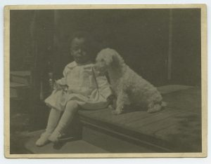 ALT:Robert Richards sits with his dog, Reddy, c. 1919.