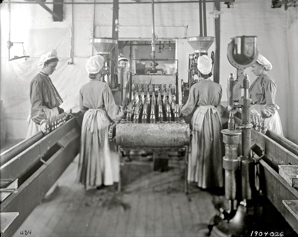 Employees fill bottles in the ketchup bottling department, 1904.