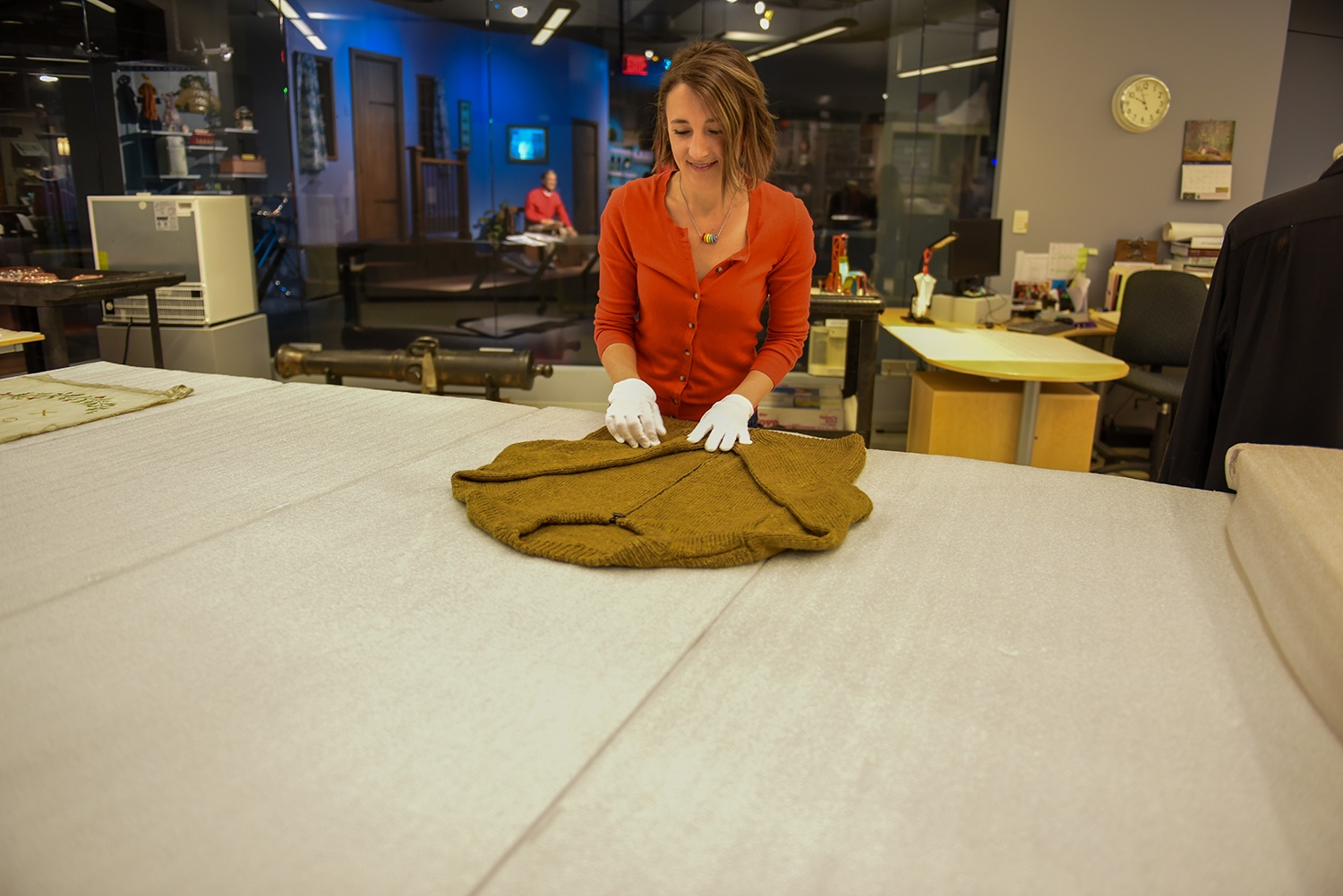 "Heinz History Center curator Emily Ruby prepares a handmade sweater owned by Fred Rogers to be added to the museum's popular ""Mister Rogers' Neighborhood"" exhibit."