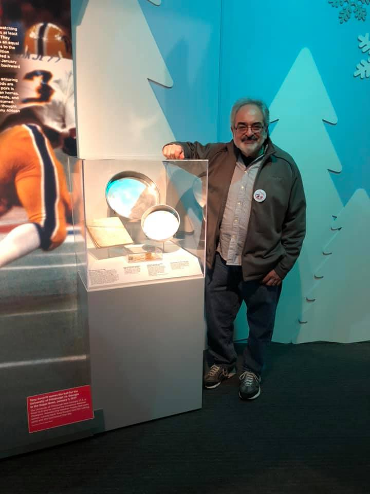 Gus Karafilis alongside his mother's home artifacts at the opening of A Very Merry Pittsburgh on Nov. 16, 2019.