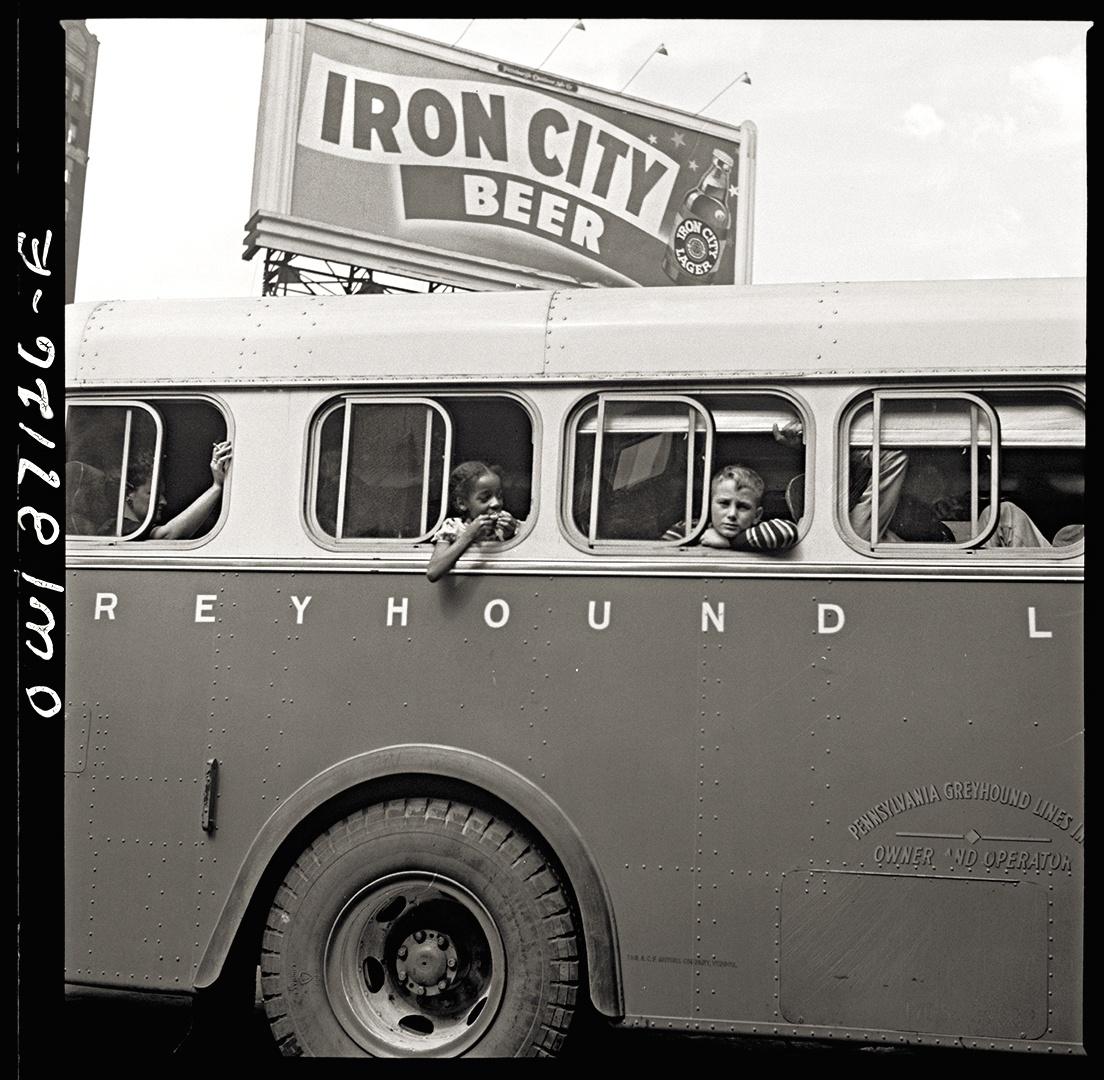 A billboard for Iron City Beer towers over a bus as it departs Pittsburgh's Greyhound terminal, 1943.