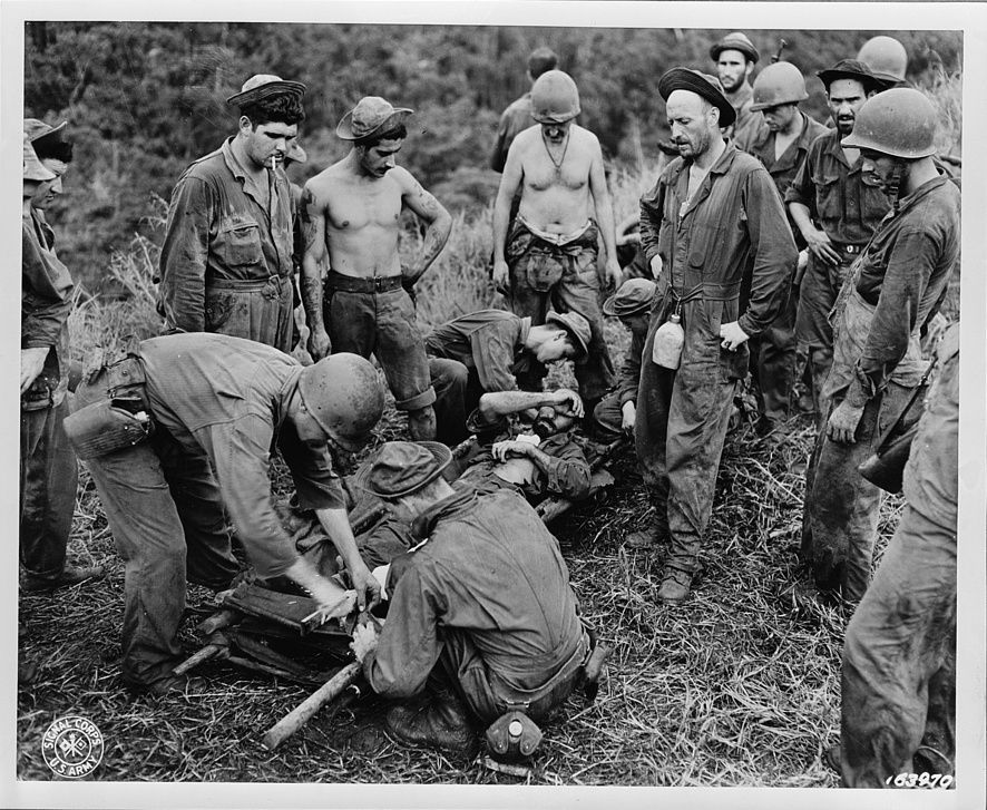 A casualty from the front line being transferred from a makeshift stretcher on Guadalcanal, between 1942-1945. Courtesy of the Office of War Information. Library of Congress, Prints and Photographs Division.