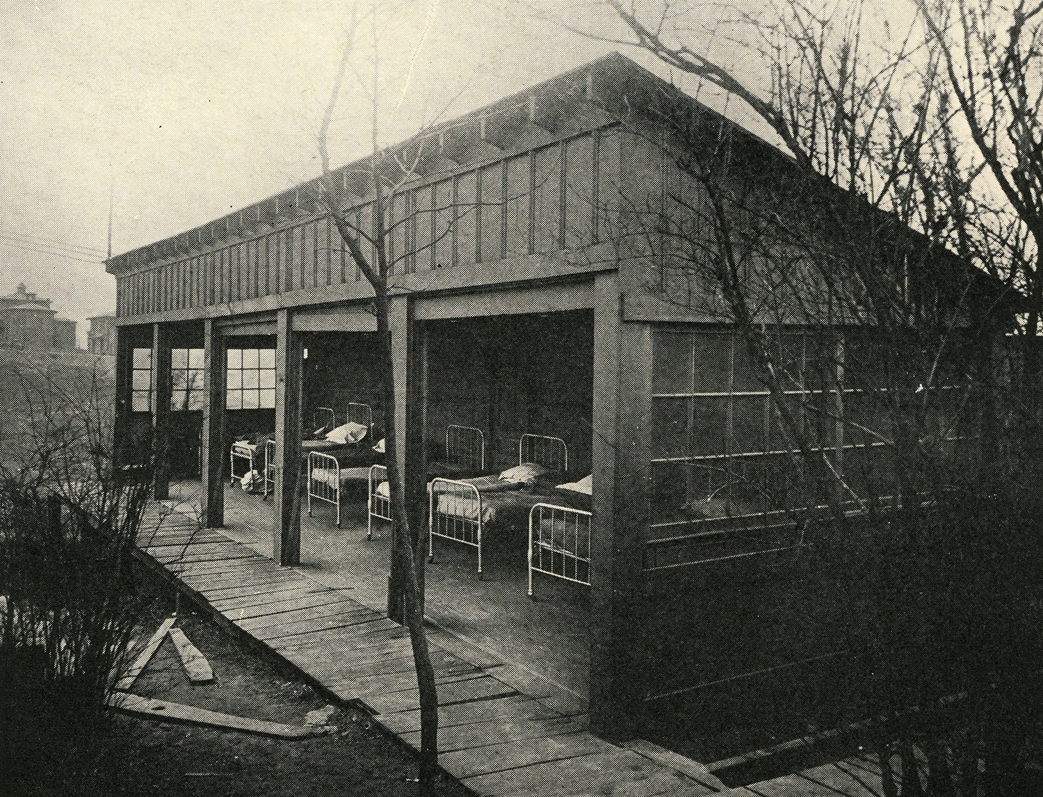 Open-air shacks with beds for patients, c. 1920.