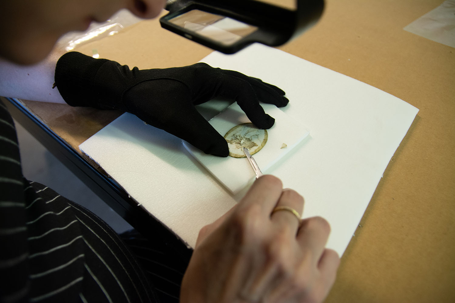 Paring down old adhesive and paper remnants. Image courtesy of Alba Art Conservation.