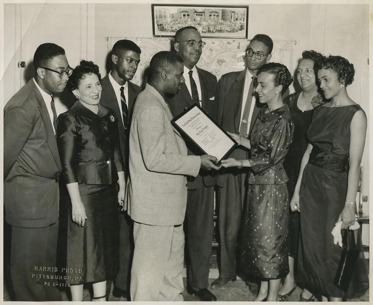 "Group portrait of four women, and five men, including one wearing light colored cross hatch patterned suit presenting certificate inscribed ""North Carolina Mutual Life Insurance Company...winner Miss Maude Hawkins..."" to woman wearing dark suit with small flower or dot pattern, in interior with map and large group photograph on wall, another version, c. 1957. Maude Y. Hawkins Photographs, MSQ 171, Detre Library & Archives at the History Center. © Carnegie Museum of Art, Charles ""Teenie"" Harris Archive."