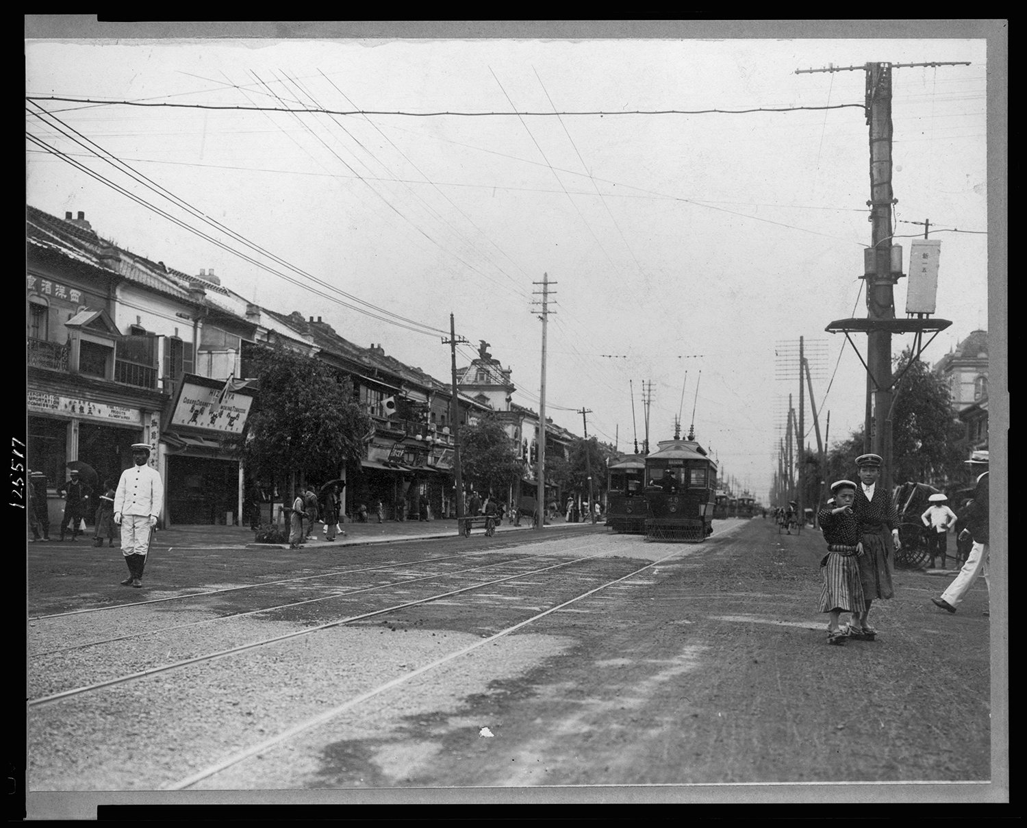 Street scene in Tokyo, c. 1905. Notice the utility poles and the streetcars in the background. This photograph was taken over a decade after Bly's visit to Japan, but it reflects many of her observations about technology and changing customs. Courtesy of the Library of Congress.