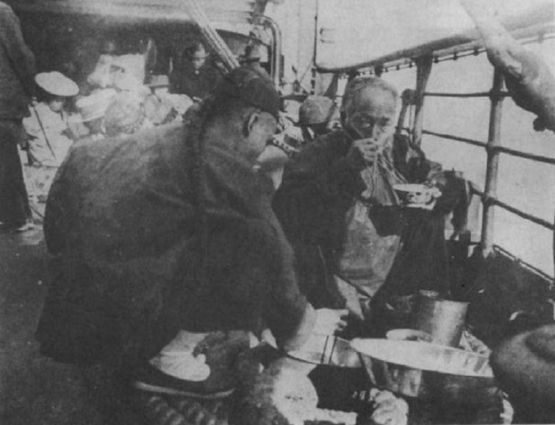 Chinese passengers eating a meal on the steerage deck, 1901. Courtesy of Wikimedia Commons.