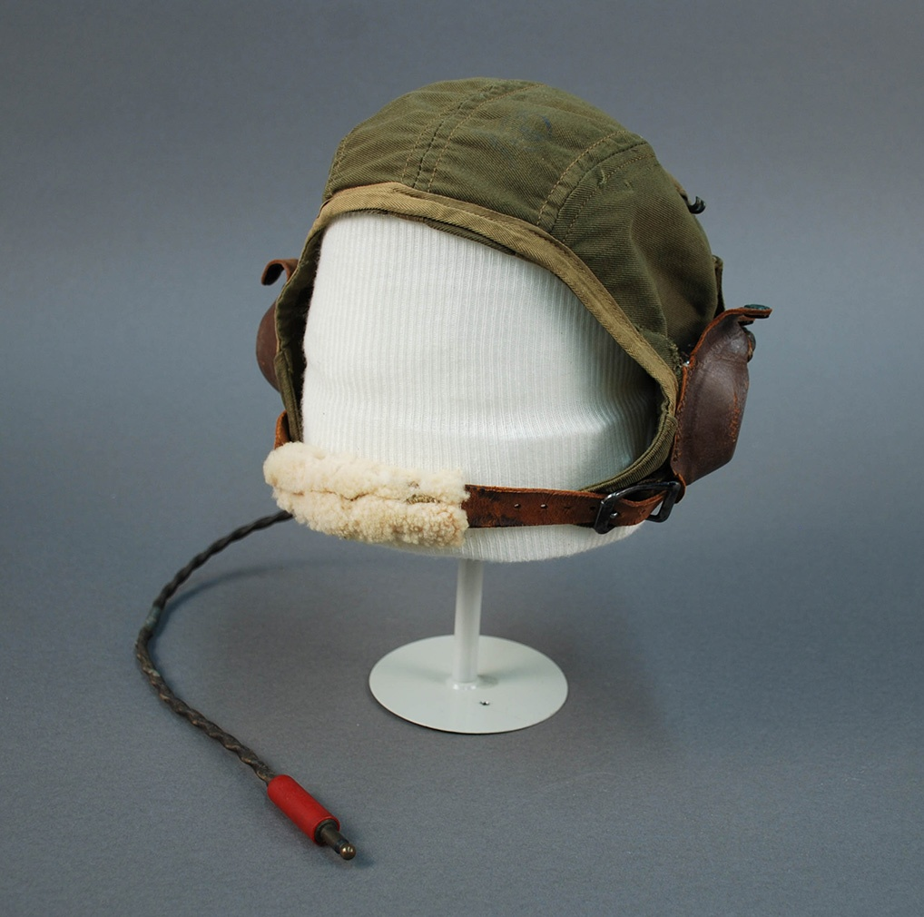 Aviator's green canvas fabric cap with earphones and chin strap, worn by William A. Johnston. Gift of Regis Bobonis.